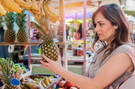 Attractive woman choosing pineapple