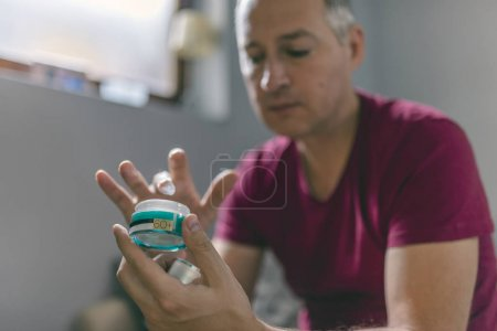 Mature man applying cosmetic product. Handsome middle aged man holding container with cream