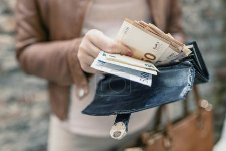 Closeup photo of stylish woman taking money out of leather purse. Spending money concept