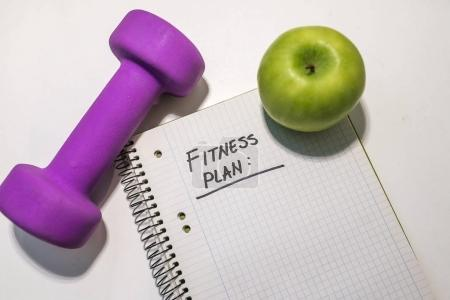fitness plan note in notepad. Dumbbell, notepad and fresh green apple