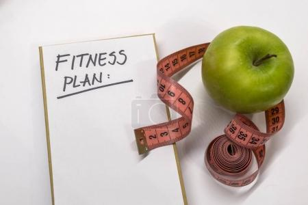 fitness plan note in notepad. Measuring tape, notepad and fresh green apple