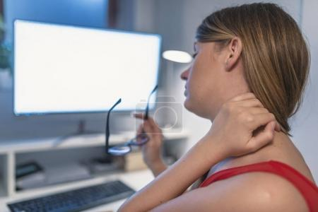 neck pain at work. Tired female office worker sitting at desk massaging her neck