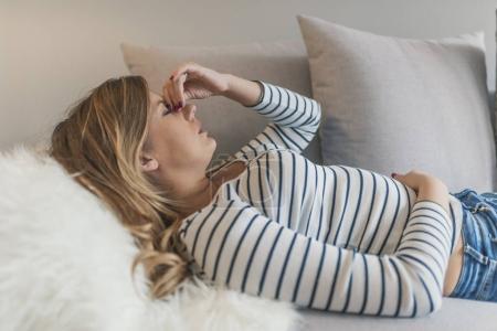Photo pour Jeune femme souffrant de maux de tête ou migraine. Douleur de fille occasionnel de sensation. Ayant une forte migraine. Triste femme enceinte ayant des maux de tête et sensation de malaise sur lit - image libre de droit