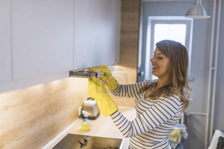 Young Woman Cleaning Cooker Hood With Rag And Detergent In Kitchen. Close up of female hands in rubber protective yellow gloves cleaning the kitchen metal extractor hood with rag. Home, housekeeping concept.