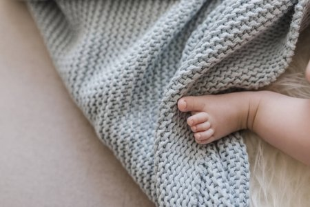 Tiny foot of newborn baby in soft selective focus.