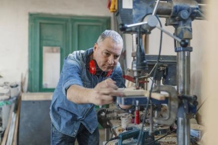 Photo pour Homme ingénieur support près vu la machine à fabriquer des meubles à l'atelier des charpentiers. Affaires à la main à l'usine de petits meubles - image libre de droit