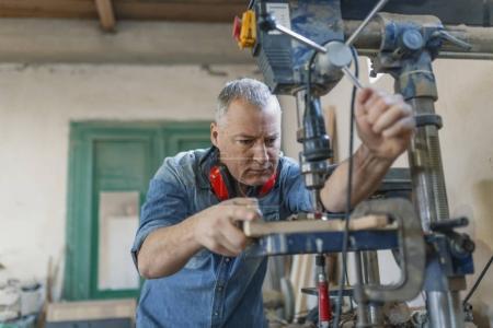 Foto de Hombre Ingeniero soporte cerca de Sierra de máquina para hacer los muebles en el taller de carpinteros. Negocio hecho a mano en fábrica de muebles pequeños - Imagen libre de derechos