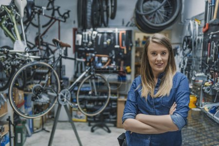 Portrait of female technician smiling and standing with folded arms in bicycle repair shop.