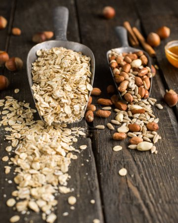 Natural products in iron vintage scoops on wooden granary boards. Hercules flakes (oat flakes), sunflower seeds, fresh peanuts, hazelnuts, honey. Ingredients for granola or oatmeal. Useful breakfast.