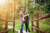 Couple of happy young people in a nature. Couple enjoying walk on pathway in forest.