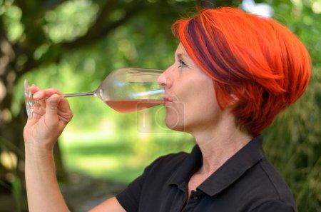 Redhead woman enjoying a glass of champagne