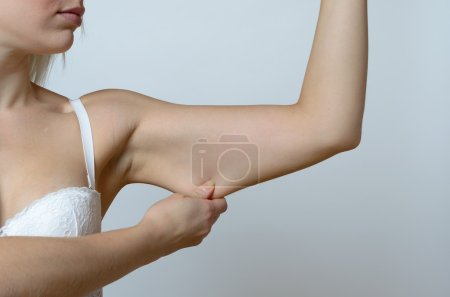 Photo for Young woman displaying the loose skin or flab due to ageing on her upper arm pinching it between her fingers, close up view - Royalty Free Image