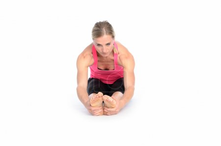 Supple fit young woman grasping her feet