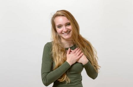 Photo pour Jeune femme montrant son sincère gratitude et les remerciements enlacer ses mains à son coeur avec un sourire heureux - image libre de droit