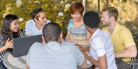 Photo pour Groupe multiculturel de gens discutent de l'ordinateur portable à la table à l'extérieur - image libre de droit