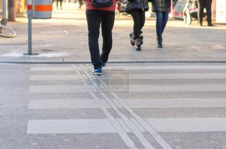 Photo for People crossing a zebra crossing for pedestrians in an urban street in a low angle view of their legs as they step off the sidewalk - Royalty Free Image