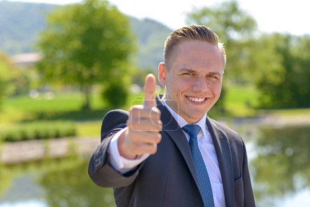 Photo for Young professional man with a beaming smile outdoors giving a thumbs up gesture of approval and success - Royalty Free Image