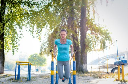 Woman working out on parallel bars
