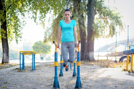 Sporty woman exercising on parallel bars
