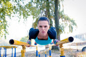 Athletic woman training on parallel bars
