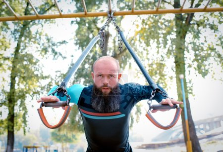 Man training with straps in the park