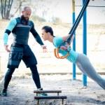 Постер, плакат: Slim woman with her trainer doing exercises