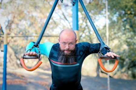 Photo for Man training with sport equipment in outdoors gym in the park - Royalty Free Image