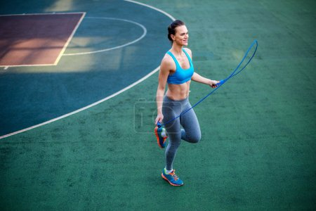 Photo for Muscular athletic woman using jump rope for their workout on stadium - Royalty Free Image