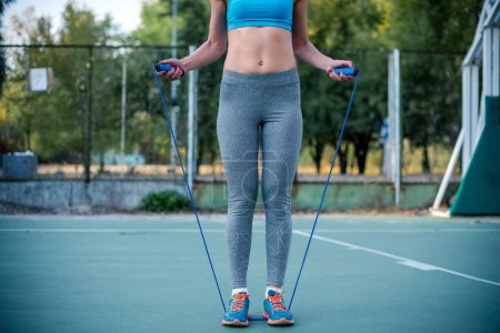 Photo for Woman in sportswear exercising with jump rope on the stadium - Royalty Free Image