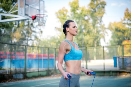 Athletic woman using jump rope
