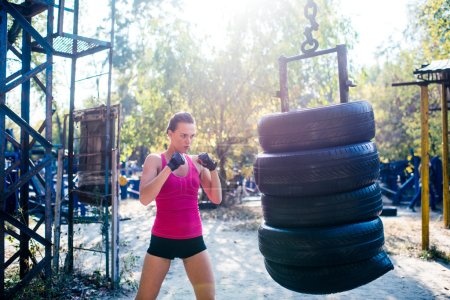 Photo for Woman boxer doing cross kick working out outdoors. - Royalty Free Image