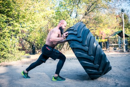 Photo for Athletic man lifting a heavy tire in outdoor gym - Royalty Free Image