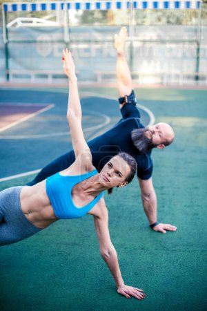 Couple in sportswear doing side plank