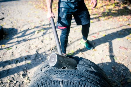 Man exercising with hammer and tire