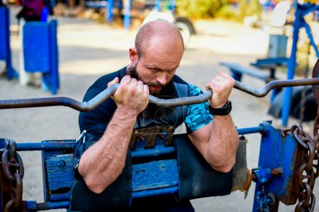 Photo for Muscular man doing weightlifting exercises in outdoor gym - Royalty Free Image