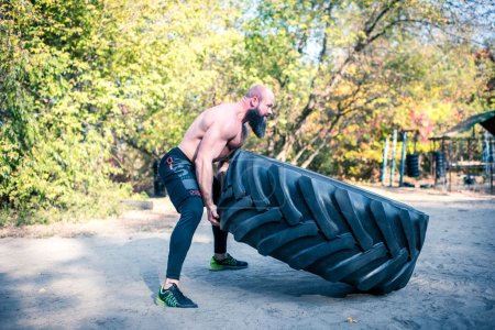 Strong man working out with tractor tire