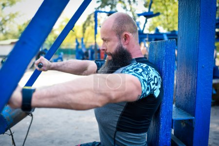 Photo for Side view of man in sportswear training on chest press equipment in outdoor gym - Royalty Free Image