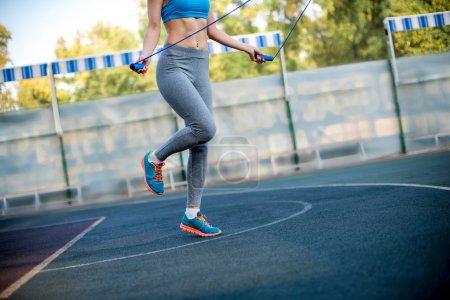 Photo pour Plan recadré d'une femme faisant de l'exercice avec saut à la corde au stade - image libre de droit