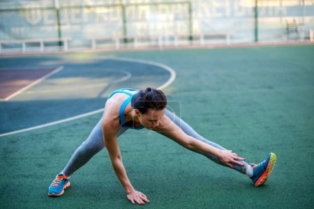 Photo for Sporty woman stretching body before workout on the stadium - Royalty Free Image