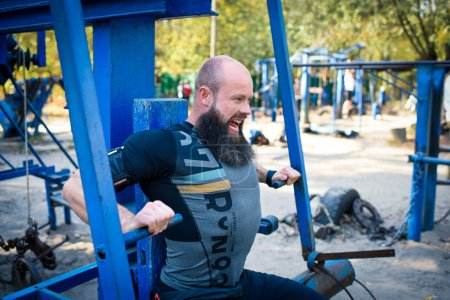 Photo for Side view of muscular man training on chest press equipment in outdoor gym - Royalty Free Image