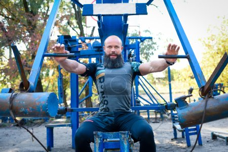 Photo for Muscular man training on chest press equipment in outdoor gym - Royalty Free Image