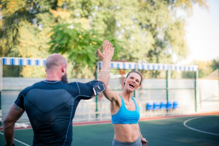 Photo for Athletic couple giving high five during workout on the stadium - Royalty Free Image