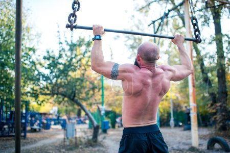 Photo for Rear view of man doing chin-ups in outdoor gym - Royalty Free Image