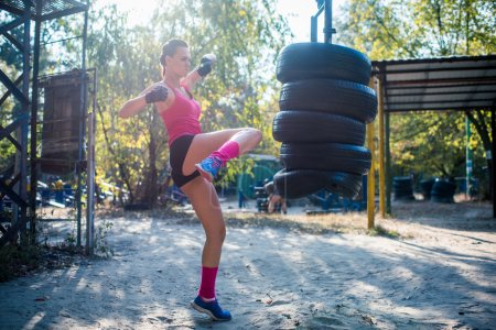 Photo for Woman practising kickboxing performing a leg kick working out outdoors. - Royalty Free Image