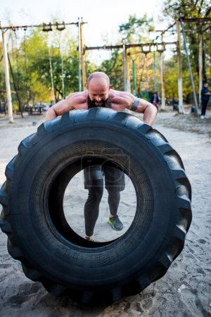 Man lifting heavy tire