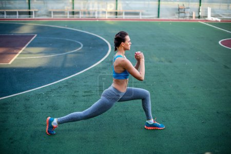 Photo for Side view of woman in sportswear training on stadium - Royalty Free Image
