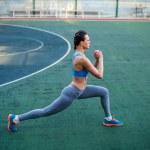 Side view of woman in sportswear training on stadi...