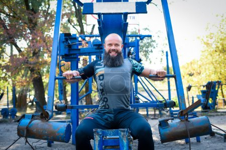 Photo for Strong bearded man doing exercises for chest on special equipment in outdoor gym - Royalty Free Image