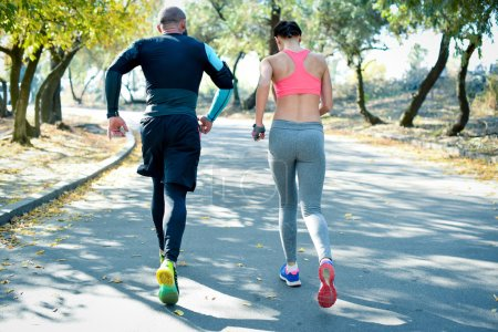Photo for Rear view of athletic couple jogging together in the park - Royalty Free Image