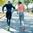 Rear view of athletic couple jogging together in t...